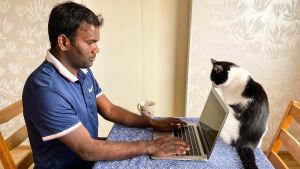 En man sitter vid köksbordet och skriver på en bärbar dator. En katt snusar på datorn.