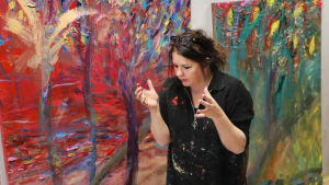 Nanna Susi maalauksiensa edessä.