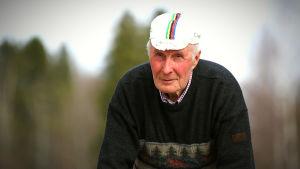 Harry Hannus med en gammal cykelkeps på huvudet vid vägrenen
