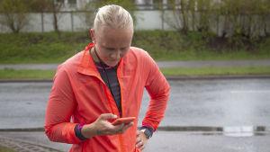 Amanda Kainulainen kollar mobilappen för att se hur snabbt hon löpt.