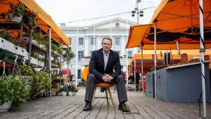 Jan Vapaavuori sitter på en stol på Salutorget, i gången mellan två rader av orangea försäljningsstånd.