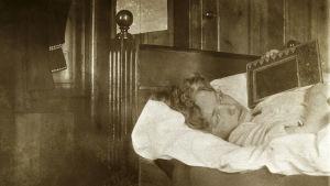 Edith Södergran ligger på sjukbädd med typ en radio ? på bröstet. Ser in i kameran. Kudde under huvudet.