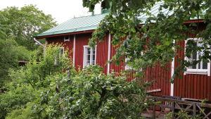 Ett rött trähus med vita knutar i Raunistula.