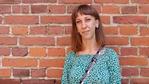 Kristina Huhtasalo är klädd i en grön tröja och står framför en tegelvägg.