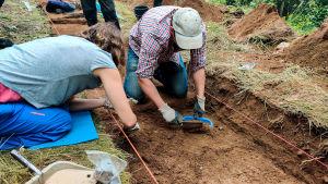 En man och en kvinna gräver vid en arkeologisk utrgrävning.