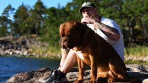 Robert Helenius njuter av solen med sin hund Bulten.