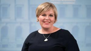 Annika Saarikko poserar mot  en blå bakgrund.