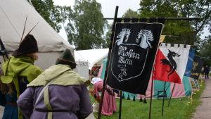 Två figurer klädda i medeltida kläder går förbi flaggor och tält på medeltidsmarknaden i Åbo.