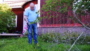 En man går omkring i gräset med en metalldetektor. I bakgrunden syns ett gammalt, rött trähus.