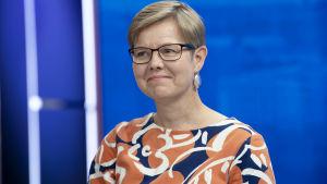 Miljöminister Krista Mikkonen (Gröna) i närbild i en studiomiljö. Hon är i närbild och ler snett mot kameran i en färggrann skjorta. Studioväggen är blå.