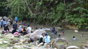 Inhemska turister svalkar av vid en bäck i utkanten av en malaysisk naturpark. Turisterna glömmer ibland bort att använda ansiktsskydd och att de inte ska vara alltför nära varandra.