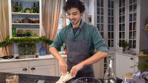 En kock som står i ett kök och bakar ett bröd.