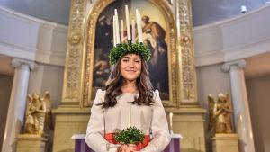 Ingrid Enckell står i domkyrkan i luciautstyrsel.