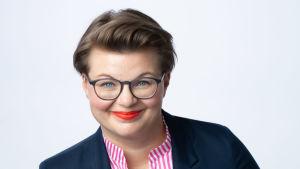 En leende kvinna med glasögon.