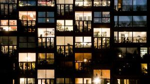 Bild på byggnad med ett flertal fönster som är upplysta så man ser in i lägenheterna.