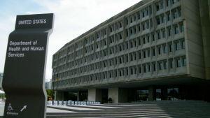 En grå betongfasad i fem våningar med små fönster. I förgrunden en skylt som upplyser att här finns USA:s hälso- och socialministerium.