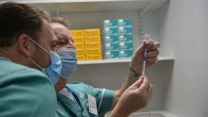 Två personer granskar ett coronavaccin.