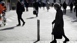 Dam med käpp promenerar i Helsingfors.
