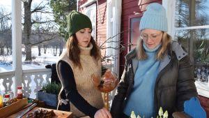 Två kvinnor gör mat utomhus