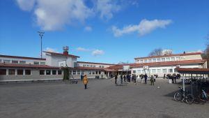 Många barn och en lärare i gul jacka vistas en solig vårdag på en skolgård med basketbollställningar och cykleparkering.