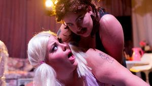 Skådespelarna Josefine Fri i blond peruk och Emelie Zilliacus i hockeyfrilla och mustasch ligger på ett scengolv med starka strålkastare i bakgrunden.