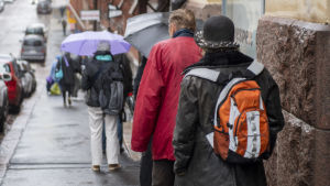 Människor som står i en brödkö. Flera har paraply efetrsom det regnar. Personerna står med ryggen mot kameran.