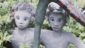 Två statyer föreställande barn som sitter under en stor svamp.