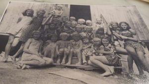 """""""Internerade barn på andra barackens trappa sommaren 1945""""  Ett svartvitt foto"""