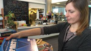 Kvinnlig bibliotekarie sorterar bredspel.