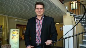 Mikko Ollikainen står på en spiraltrappa i kommunkanslit i Vörå