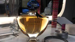En flaska Shalimar-parfym på ett sminkbord.