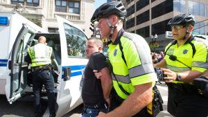 En motdemonstrant förs iväg av polisen under demonstrationen i Boston.