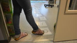 En barnträdgårdslärare pekar med sin fot på siffror på golvet i en förskola.