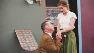 Skådespelare: Den ena föreställer Pekka Lipponen som knäböjer framför en kvinna klädd i grön kjol och vit blus.