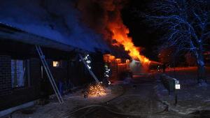 Radhus länga brinner och eld kommer ut från bostäder, brandmän på stegar, snö på marken.