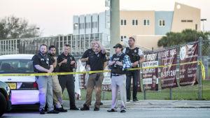 En grupp poliser står på vakt utanför skolbyggnaden.