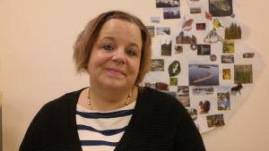 Andrea Schmidt sitter framför en vägg med små bilder