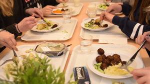 Elever som äter potatis och fiskbullar i en skolmatsal.