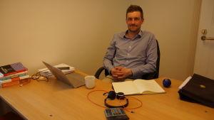 en man som sitter vid ett arbetsbord