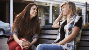 Två kvinnor sitter på en bänk och talar, ser glada ut.