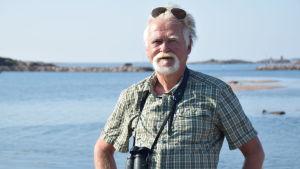 En man står med en kikare runt halsen. I bakgrunden syns hav och öar. Mannen är vithårig och har vitt skägg. På huvudet har han solglasögon