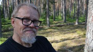 Juhani Karhumäki, en man med gråvitt hår, mustasch och skägg, samt glasögon med svarta bågar.