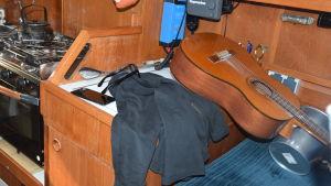 insidan av en segelbåt, med en huppari och en gitarr