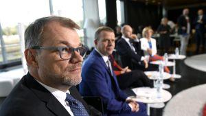 Juha Sipilä i förgrunden, Petteri Orpo, Sampo Terho och Anna-Maja Henriksson syns suddigt i bakgrunden. Partiledarna deltar i en debatt arrangerad av Alma Media.