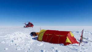 Ett tält och en helikopter på Grönland. Det enda som syns är snö.