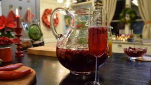 En stor glaskanna med en kall glöggdrink, samt ett champagneglas med glöggdrink.