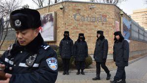 Kinesisk polis patrullerar utanför Kanadas ambassad i Peking. Det har förekommit flera ilskna protester utanför ambassaden.