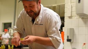 En man i vita kläder och svart keps dekorerer bakelser i ett bageri.