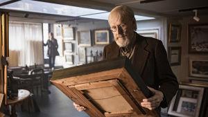 Konsthandlaren Olavi undersöker en av sina tavlor.