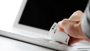 En hand med två ess vilar på en vit, bärbar, dator.